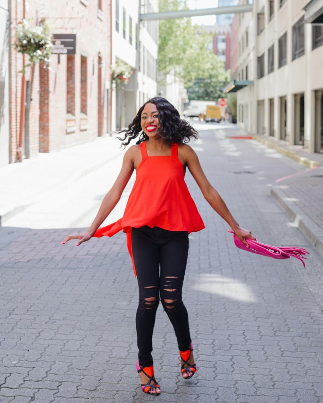 Twirling in a free flowing asymmetrical top and distressed denim