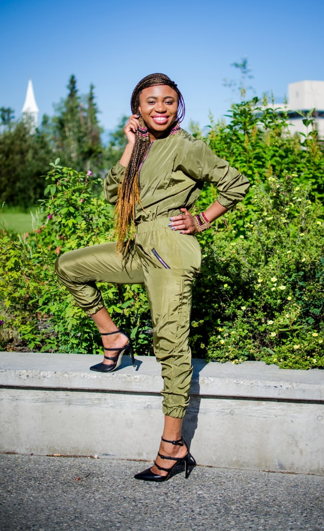 Olive Bomber Jumpsuit   Fashion blogger rocking a one-piece, long-sleeve jumpsuit paired with a multi strap sandals for a chic street style outfit. Click to check out more of her fun and affordable style.