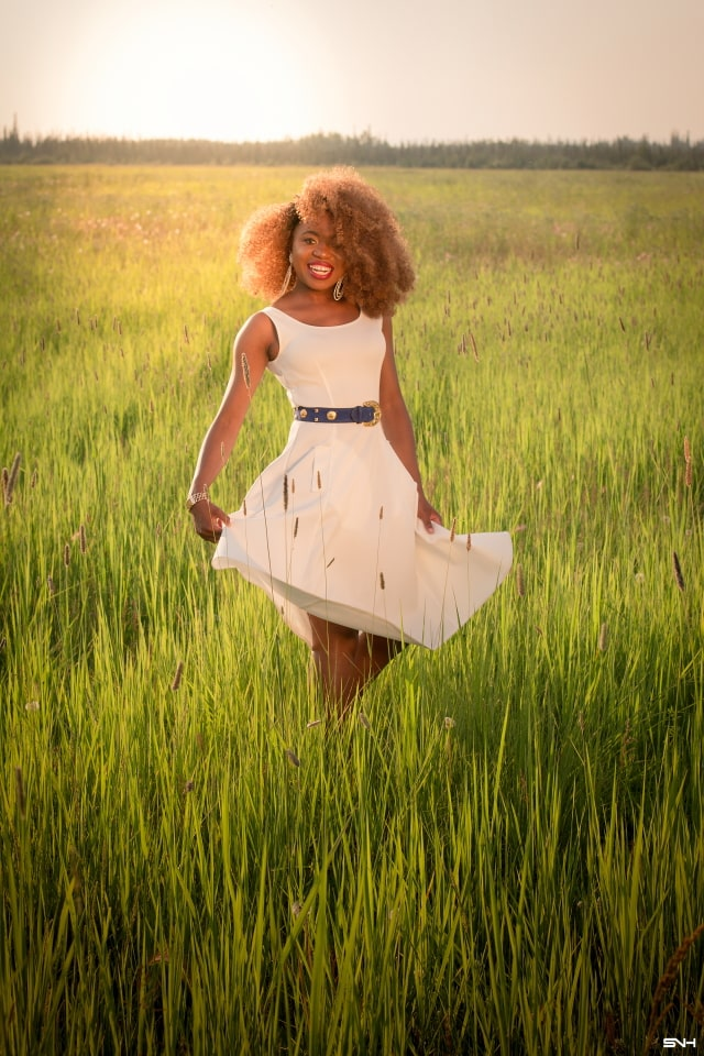 Can't get over her stunning white summer dress! ? Twirling in the prairie fields. Her sleeveless A-line midi dress has the perfect flare. Bold statement hoop earrings and embellished blue belt perfects her outfit. A dress that you can dress up or down! Little white dress, flare dress, Dress with flare, White dress, Summer dress, Formal dress, Modest dress, Wedding guest outfit, Black girl, Classy dress, womens style