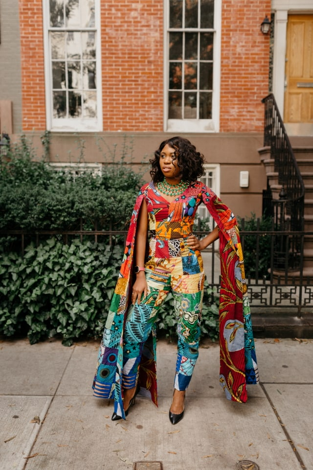 How I love the dramatic cape sleeves of this rainbow patchwork ankara jumpsuit. I'm sure she turned heads when she showed up to New York Fashion Week dressed like this. With simple wavy hair, black pumps and green statement necklace to match, it'll be no surprise if the media swoons over her. Stunning NYFW Fall/Winter 2017 outfit #NYFW #NewYorkFashionWeek #Ankara #Kente