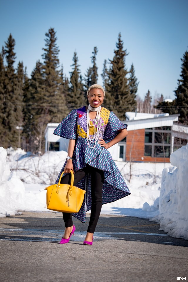 To say that African print clothes are fascinating is an understatement. This tiered African print high low top is the perfect statement blouse this summer. The rich purple, yellow and blue colors paired with fitted black denim and a vibrant satchel is a winner. Can't get enough! Check out this blogger's 30 days of African print fashion! #ankara #africanprint #ankarafashion #nigerian Dashiki, African print dress, African fashion, African women dresses, African prints, Nigerian style